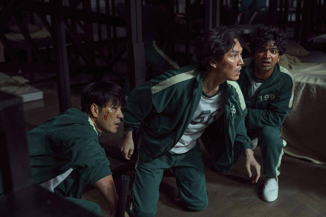 """This undated photo released by Netflix shows South Korean cast members, from left, Park Hae-soo, Lee Jung-jae and Anupam Tripathi in a scene from """"Squid Game."""" Squid Game, a globally popular South Korea-produced Netflix show that depicts hundreds of financially distressed characters competing in deadly children's games for a chance to escape severe debt, has struck a raw nerve at home, where there's growing discontent over soaring household debt, decaying job markets and worsening income inequality. (Youngkyu Park/Netflix via AP)"""
