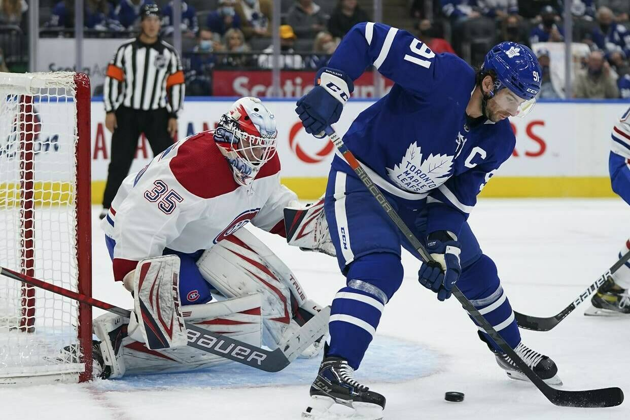 Toronto Maple Leafs forward John Tavares (91) tries to tip the puck past Montreal Canadiens goaltender Sam Montembeault (35) during first period NHL pre-season hockey action in Toronto on Tuesday, October 5, 2021. THE CANADIAN PRESS/Nathan Denette