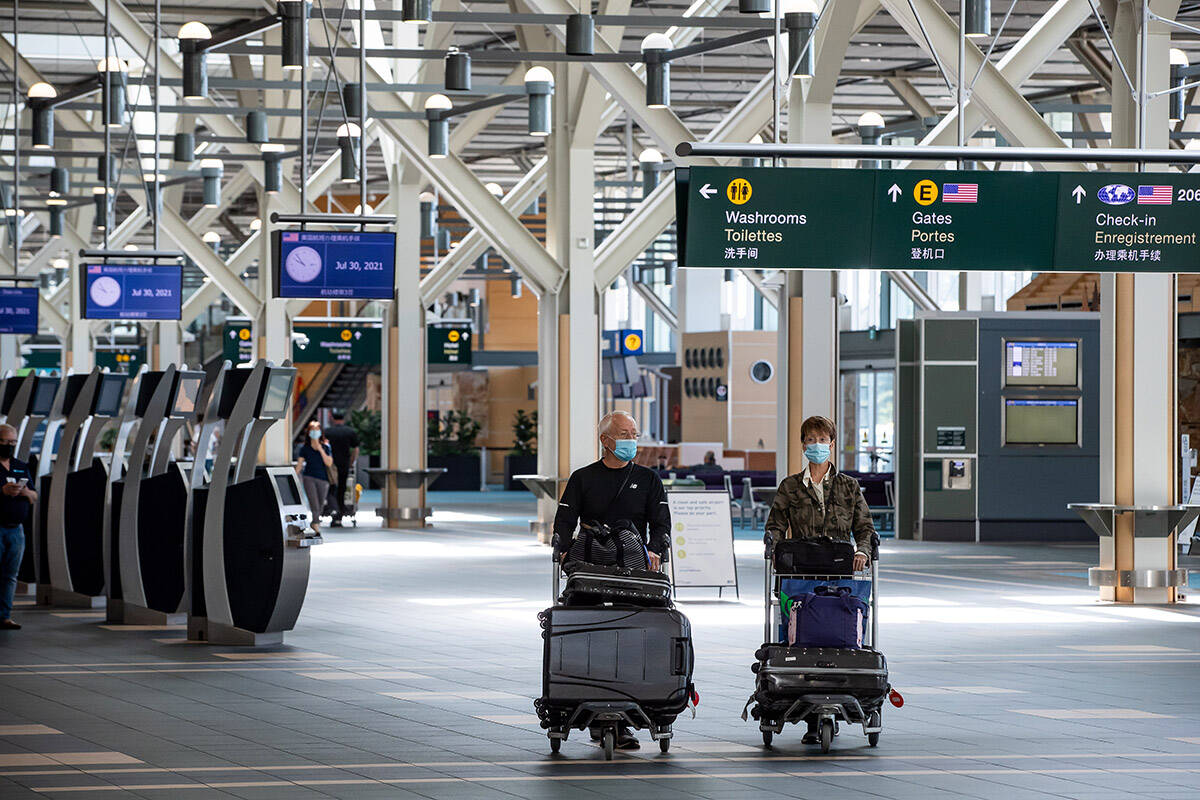 FILE – Travellers pushing luggage on carts walk through Vancouver International Airport, in Richmond, B.C., on Friday, July 30, 2021. THE CANADIAN PRESS/Darryl Dyck